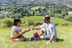 Licensed to London News Pictures. 01/06/2021. Dorking, UK. On the hottest day of the year so far, school teachers Sarah and Simon Head from Salisbury stop for an ice lolly while doing the 8 mile Box Hill Hike walk on Box hill, Surrey this morning. The Met Office have forecast very warm weather for the South East and London this week with temperatures predicted to hit up to 26c today and over 27c tomorrow. Photo credit: Alex Lentati/LNP