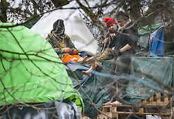 © Licensed to London News Pictures. 28/01/2021. London, UK. A group of HS2 Rebellion protesters in bare feet sit atop the remains of their camp in Euston Square Gardens. Protestors are resisting a police operation to remove them for a second day. It is reported the protesters have built a 100ft tunnel under the gardens. Photo credit: Peter Macdiarmid/LNP