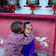 Young brother and sister lingering a Buddhist temple.