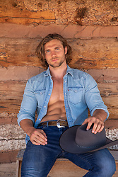 hot cowboy with an open shirt by a rustic cabin