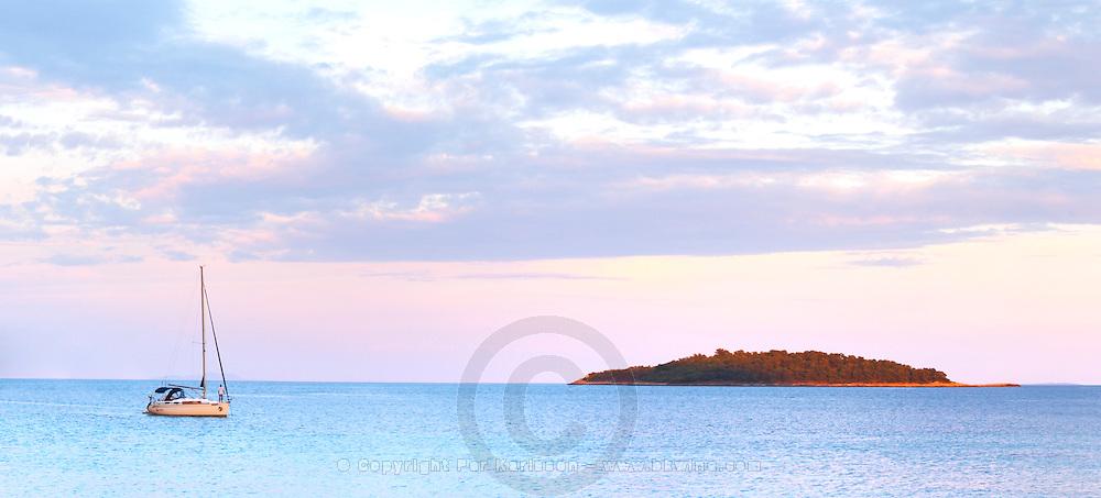 Panorama of the bay a sailing boat moored in the bay island in the background, off the Korcula island at sunset. Prizba village. Korcula Island. Prizba, Riva Apartments, Danny Franulovic. Korcula Island. Dalmatian Coast, Croatia, Europe.