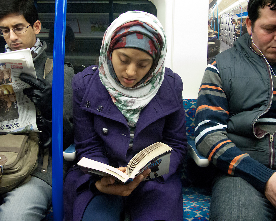 Portrait of a muslim girl reading a book on the London Underground Network
