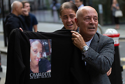 Charlotte Huggins' father holds up a T-shirt with his daughter's face on it as her family and friends celebrate outside the Old Bailey in London following the guilty verdict of Michael Rolle, 34, of stabbing mother-of-one, 33, at her home in Kennington. He will be sentenced tomorrow (19 July). London, July 18 2019.