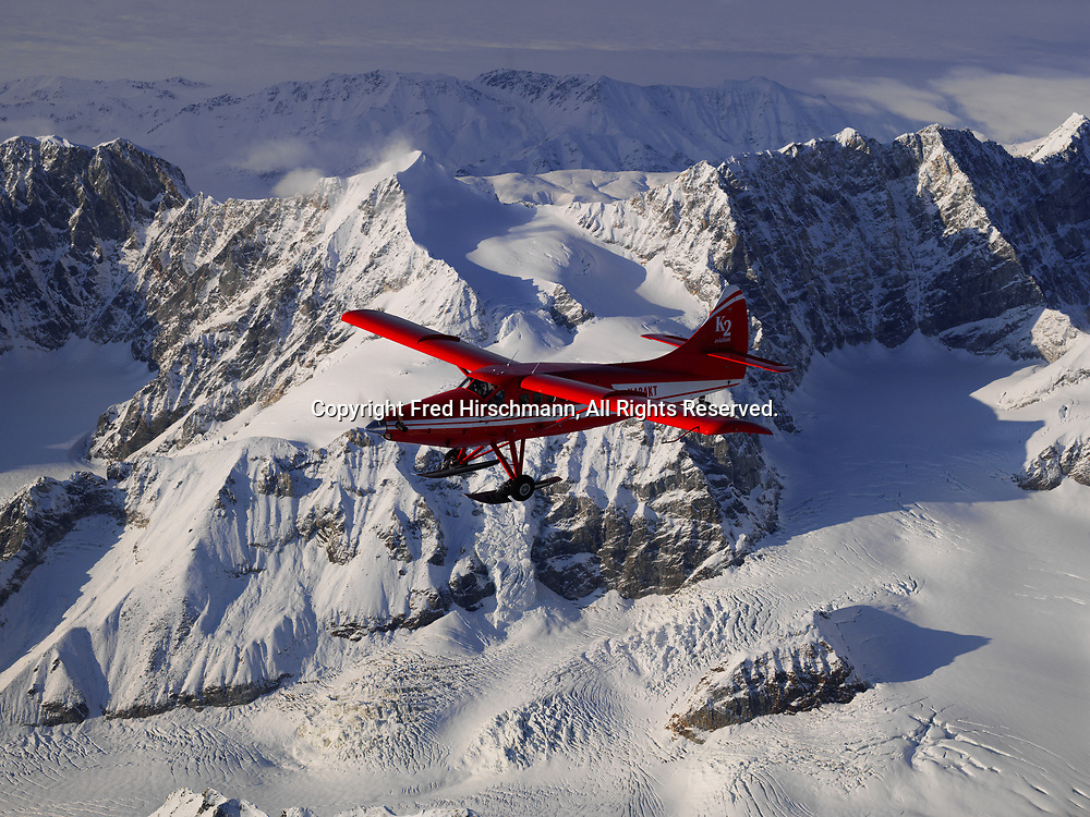 K2 Aviation's Turbo Otter on wheel skis flying above the Alaska Range in Denali National Park, Alaska.