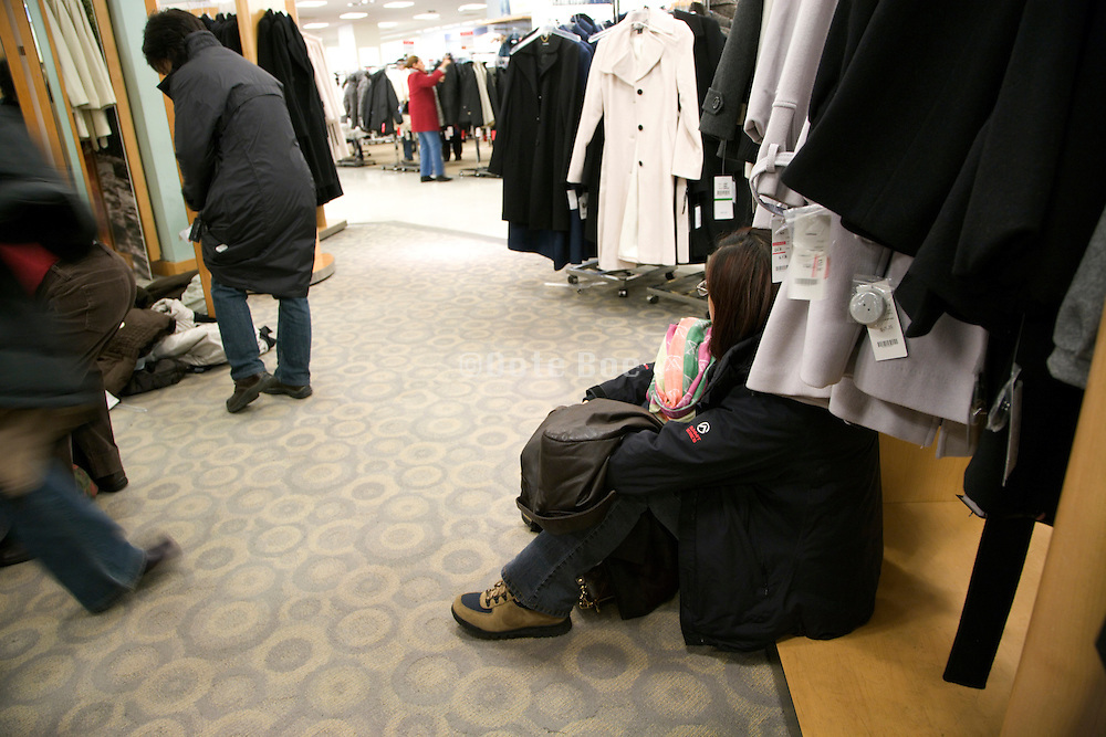 young woman taking a seat between coats while shopping for a coats during end of year sale