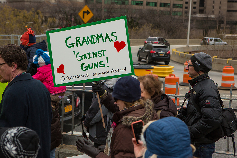 "A woman carries a placard reading ""Grandmas against guns."""