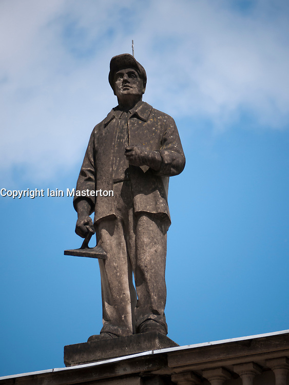 Statue of worker on old apartment building on Karl Marx Allee in former East Berlin in Germany