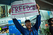 "01 JUNE 2014 - BANGKOK, THAILAND: A man screams ""freedom"" during a protest against the Thai coup at Terminal 21, a popular shopping mall in Bangkok. The Thai army seized power in a coup that unseated a democratically elected government on May 22. Since then there have been sporadic protests against the coup. The protests Sunday were the largest in several days and seemed to be spontaneous ""flash mobs"" that appeared at shopping centers in Bangkok and then broke up when soldiers arrived. Protest against the coup is illegal and the junta has threatened to arrest anyone who protests the coup. There was a massive security operation in Bangkok Sunday that shut down several shopping areas to prevent the protests but protestors went to malls that had no military presence.    PHOTO BY JACK KURTZ"
