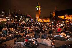 "© Licensed to London News Pictures. 02/12/2015. London, UK. As MP's decide in Parliament whether to vote for the UK to commence air strikes in Syria, thousands of anti-war protestors stage a ""die in"" in Parliament Square urging MPs to vote against military action.  Photo credit : Stephen Chung/LNP"