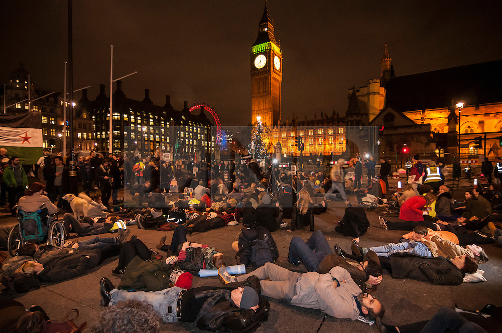 """© Licensed to London News Pictures. 02/12/2015. London, UK. As MP's decide in Parliament whether to vote for the UK to commence air strikes in Syria, thousands of anti-war protestors stage a """"die in"""" in Parliament Square urging MPs to vote against military action.  Photo credit : Stephen Chung/LNP"""