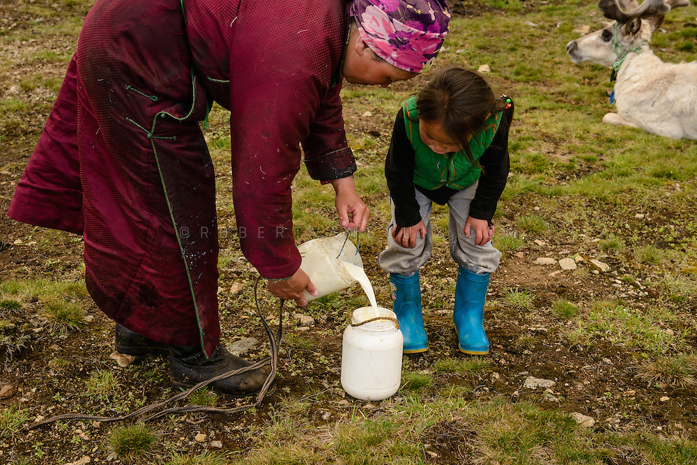 Mother and daughter pouring freshly collected reindeer milk in a Dukha (Tsaatan) reindeer herder community, Mongolia. One reindeer yields approximately one cup of milk per day, used for cheese making and milk consumption. Photo © Robert van Sluis