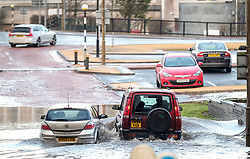 Storm Ciara, 9 February 2020<br /> <br /> Pictured: A car is abandoned after becoming stuck in flood waters in Livingston, West Lothian. A Land Rover decided to chance going around the stricken vehicle.<br /> <br /> Alex Todd | Edinburgh Elite media