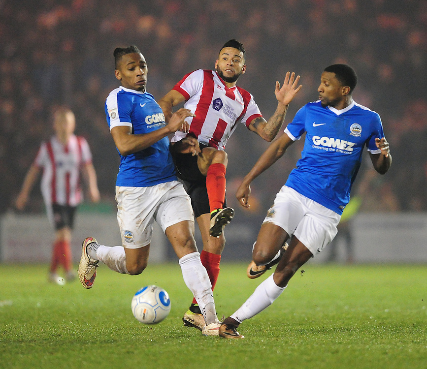 Lincoln City's Nathan Arnold vies for possession with Dover Athletic's Aswad Thomas, left, and Dover Athletic's Tyrone Sterling<br /> <br /> Photographer Chris Vaughan/CameraSport<br /> <br /> Vanarama National League - Lincoln City v Dover Athletic - Friday 20th January 2017 - Sincil Bank - Lincoln<br /> <br /> World Copyright © 2017 CameraSport. All rights reserved. 43 Linden Ave. Countesthorpe. Leicester. England. LE8 5PG - Tel: +44 (0) 116 277 4147 - admin@camerasport.com - www.camerasport.com
