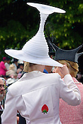 Race-goer wearing a hat like an upturned wine glass in true Ascot fashion at Royal Ascot Races