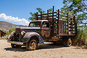 Rusting V8 truck with flat tire in Benton Hot Springs, Mono County, California, USA. Benton Hot Springs (elevation 5630 feet) saw its heyday from 1862 to 1889 as a supply center for nearby mines. At the end of the 1800s, the town declined and the name Benton was transferred to nearby Benton Station.