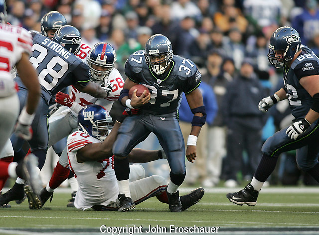 Seattle Seahawks' Shaun Alexander runs through a hole as New York Giants' Kendrick Clancy (70) reaches up to grab him and Seahawks' Mack Strong blocks Antonio Pierce (58) in Seattle Sunday, Nov. 27, 2005. On the right is Seahawks Chris Gray. (Photo/John Froschauer)