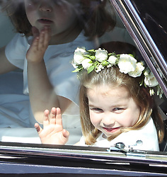 A flower girl waves to the crowd as she rides in a car to the wedding at St George's Chapel in Windsor Castle of Prince Harry and Meghan Markle.