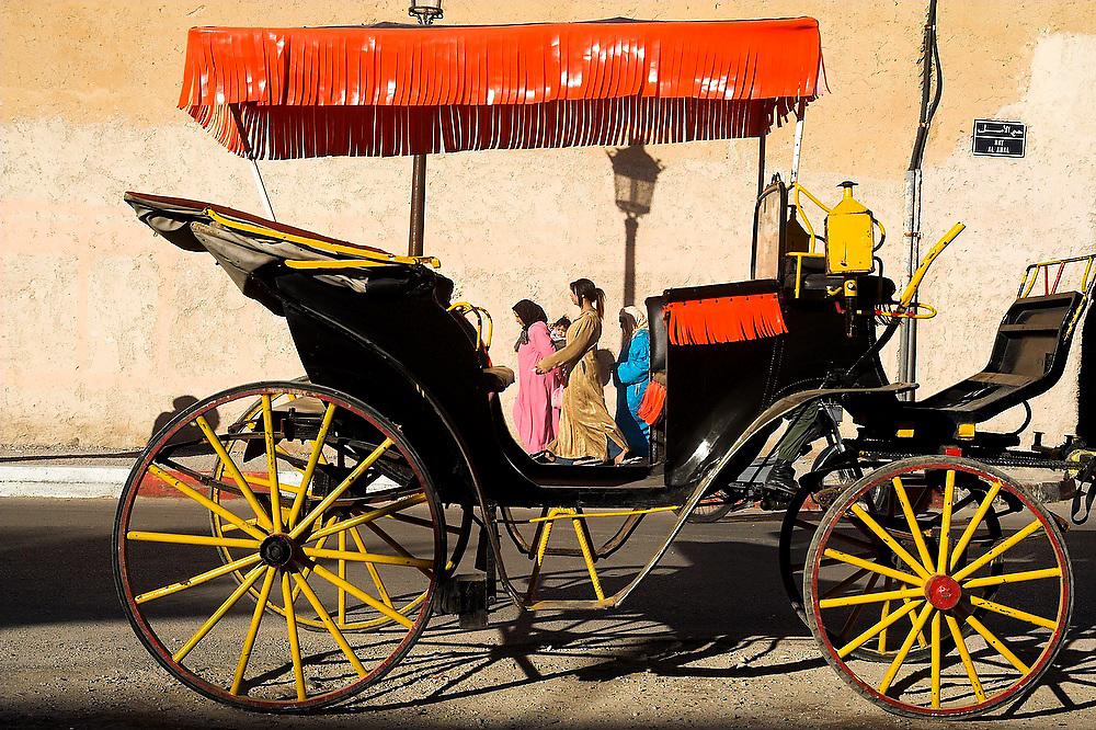 A group of women are framed by a horse-drawn carriage used for tourist rides in Meknes, Morocco.