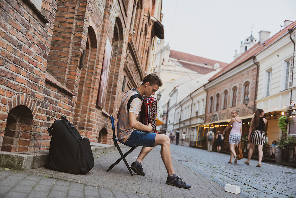 Vilnius, Lithuania - August 12, 2015: KarolisVansevicius, 18, plays the accordion, busking on Pilies Street in the old town of Vilnius, Lithuania.