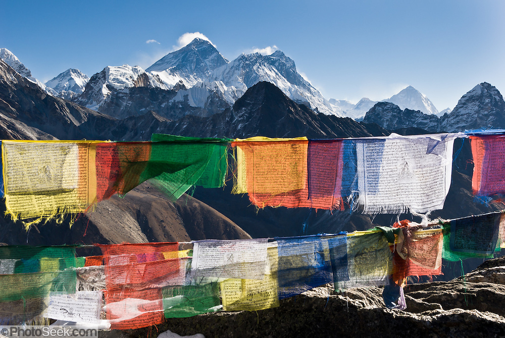 """Atop Gokyo Ri, admire Mount Everest, Himalayan peaks, and prayer flags. Mount Everest (center left; 29,029 feet / 8848 meters), the highest mountain on Earth, has the older name of Chomolungma or Qomolangma (""""Goddess Mother of the Earth"""" in Tibetan). To the right are Lhotse and Makalu (both higher than 8000 meters). In 1865, Andrew Waugh, the British surveyor-general of India named the mountain for his chief and predecessor, Colonel Sir George Everest. In the 1960s, the Government of Nepal named the mountain Sagarmatha, meaning """"Goddess of the Sky"""". The mountain, which is part of the Himalaya range in High Asia, is located on the border between Nepal and Tibet, China. These colorful Tibetan Buddhist prayer flags invoke compassion. Sagarmatha National Park was created in 1976 and honored as a UNESCO World Heritage Site in 1979. Published in """"Light Travel: Photography on the Go"""" book by Tom Dempsey 2009, 2010."""