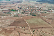 Aerial view of a rural village surrounded by agricultural fields near Marrakech, Morocco.