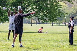 © Licensed to London News Pictures. 16/04/2020. London, UK. Men weight training on a warm Spring day as Police patrol Primrose Hill enforcing lockdown rules on social distancing and exercise. Meanwhile, Pret A Manger and other coffee shops in London start to reopen and Ministers consider when and how the lockdown will finish as politicians are warned that the UK could face the worst recession in 300 years. Photo credit: Alex Lentati/LNP