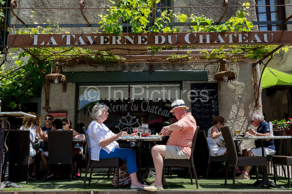 A couple eat lunch at a taverne restaurant, on 27th May, 2017, in Carcasonne, Languedoc-Rousillon, south of France. Situated on the right bank of the Aude, the City, a medieval village that is still inhabited, has 52 towers and two concentric walls totalling 3 km in length.