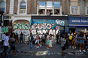People in flats above Ladbroke Grove in Notting Hill Carnival on 25th August 2019 in West London, United Kingdom. A celebration of West Indian / Caribbean culture and Europes largest street party, festival and parade. Revellers come in their hundreds of thousands to have fun, dance, drink and let go in the brilliant atmosphere. It is led by members of the West Indian / Caribbean community, particularly the Trinidadian and Tobagonian British population, many of whom have lived in the area since the 1950s. The carnival has attracted up to 2 million people in the past and centres around a parade of floats, dancers and sound systems.