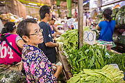 "03 OCTOBER 2012 - BANGKOK, THAILAND:      A woman shops for vegetables in Khlong Toey Market in Bangkok. Khlong Toey (also called Khlong Toei) Market is one of the largest ""wet markets"" in Thailand. Thousands of people shop in the sprawling market for fresh fruits and vegetables as well meat, fish and poultry every day.      PHOTO BY JACK KURTZ"