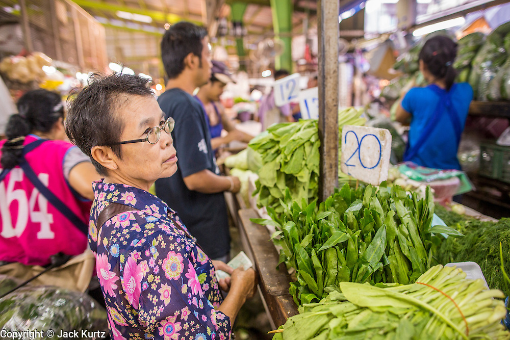 """03 OCTOBER 2012 - BANGKOK, THAILAND:      A woman shops for vegetables in Khlong Toey Market in Bangkok. Khlong Toey (also called Khlong Toei) Market is one of the largest """"wet markets"""" in Thailand. Thousands of people shop in the sprawling market for fresh fruits and vegetables as well meat, fish and poultry every day.      PHOTO BY JACK KURTZ"""