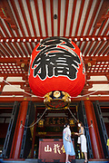 Two women stop under the ornate red-paper lantern at the entrance to the main hall of the Sensoji Buddhist temple in Asakusa, Tokyo, Japan. The temple was built during the Kamakura period in 645 CE and is the oldest and most important temple in Tokyo.