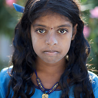 """Vijyashree Viswanathan on a morning before school at home in the fishing village of Thazanguda...Vijita (age 14) and Vijyashree (age 11) Viswanathan lost their mother and brother to the tsunami in 2004. They continue to live in the fishing village of Thazanguda with their father Viswanathan, his second wife Kayalvizhi and their two children Sanjay (age 3) and Monica (age 1). ..Until the beginning of the 2009 academic year in June, Vijita and Vijyashree attended the local Thazanguda school. This village school teaches pupils only until the 8th Standard and with Vijita now entering the 9th, it was decided that the two daughters remain together and both travel 3km to the local town school: the Government Girls High School, Venugopalapuram in Cuddalore. ..At the same time Viswanathan decided he would cease day-to-day care of his daughters and place them in the Government Home for Tsunami Children, also in Cuddalore. This was not a move welcomed by either Vijita or Vijyashree and one afternoon after just two weeks at the orphanage, the two girls ran away. At roll call in the orphanage that evening the alarm was sounded and the two sisters were eventually located in Thazanguda waiting for their father and Kayalvizhi who were both away at the time. Realising his daughters' unhappiness, Viswanathan then took them out of the Government home. ..According to her class teacher, Vijita often compares her step-mother to her mother and concludes that she wants her mother back. Vijita confides in her teachers that her stepmother is forever demanding that she and her sister Vijyashree undertake housework. This frustration at home is tempered by the genuine love both sisters have for their father and two younger siblings Sanjay and Monica. Vijita expresses a lonelyness without her mother. Pushpavalli concludes that """"Vijita wants something else beyond the love of her father and sister"""". ..Viswanathan appears genuinely to want the best for his two elder daughters. His experiment enroll"""