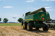 A John Deere combine is prepared for transport during the wheat harvest north of Altus AFB as an Air Force C17 transport jet practices touch and go landings in the background.