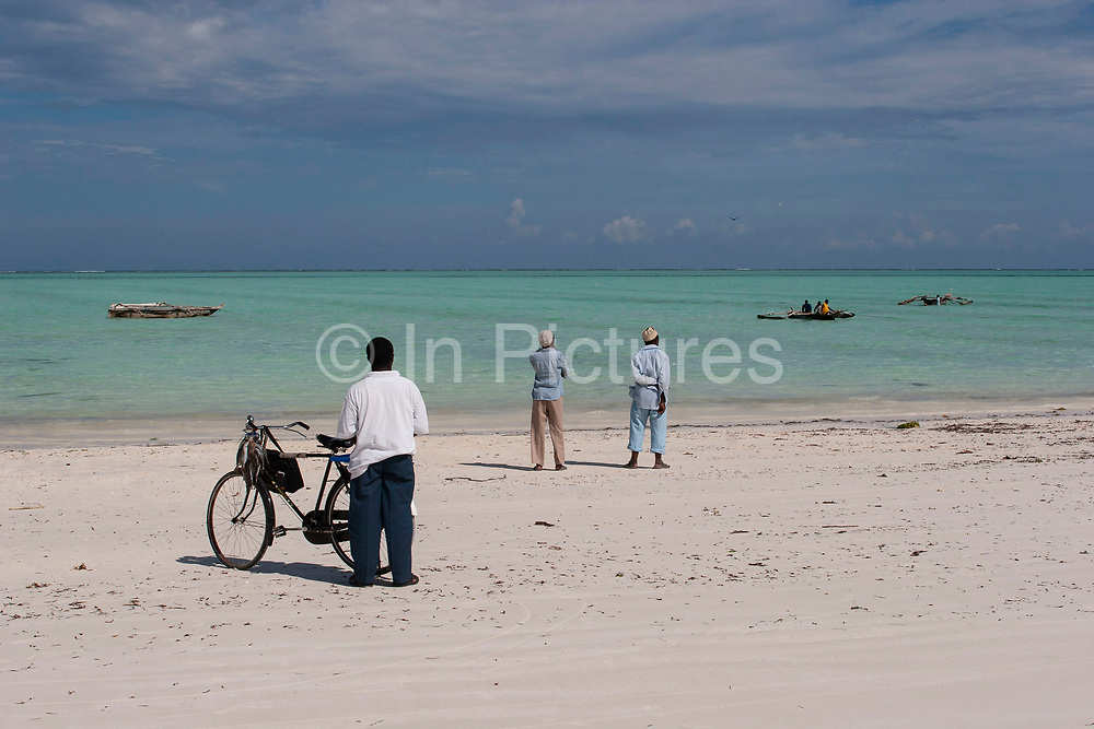 Fishermen wait on Paje beach for their fellows who have arrived back by dhow boats on 1st December 2008 in Zanzibar, Tanzania. A bicycle is a common sight on Zanzibar's beaches, as it is a quicker and flatter surface than the local roads. Zanzibar is a small island just off the coast of the Tanzanian mainland in the Indian Ocean. In part due to it's name, Zanzibar is a travel destination of mystical reputation, known for it's incredible sealife on it's many reefs, the powder white coral sand beaches and the traditional cultivation of spices.