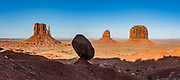 West and East Mitten Buttes and Merrick Butte punctuate the horizon beyond a balanced rock in Monument Valley Navajo Tribal Park, Arizona, USA. The Western movie director John Ford set several popular films here. This image was stitched from multiple overlapping photos.