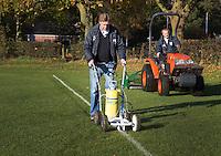 BLOEMENDAAL - Hockey op ECHT gras. Jules Hustinx, Clubmanager van HC Bloemendaal trekt de lijnen. Hidde Maas en Arie Goote maaien het gras. COPYRIGHT KOEN SUYK
