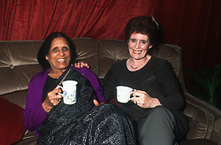 Carer sitting on sofa drinking tea with elderly woman,