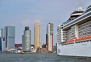 Nederland, Rotterdam, 5-5-2017 Een cruiseschip de van de zwitserse rederij MSC meert af bij Cruiseport Rotterdam aan de Wilhelminakade in de Rotterdamse haven. Uitzicht op zuiderlijk deel Rotterdam, Rotterdam zuid, stadsdeel Kop van Zuid, rivier de Maas, hoogbouw, skyline en cruiseschip aan de wilhelminakade. Foto: Flip Franssen