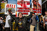 Fundamentalist Christians march down Bourbon Street  carrying their huge placards with accusatory and inflammatory rhetoric: ADULTERERS, FORNICATORS; HELL, during Mardi Gras on 25th February 2020 in New Orleans, Louisiana, United States. Busloads of  zealots show up each year just before Carnival. They rally on the outskirts of the French Quarter, driving each other into religious frenzies, then march into the French Quarter dragging huge wooden crosses and evangelising the amused crowd with a missionary zeal.