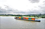 Nederland, Nijmegen, 3-8-2017Binnenvaartschip, beladen met containers, vaart over de Waal langs de ooijpolder en de uitlopers van de stuwwal uit de ijstijd.FOTO: FLIP FRANSSEN