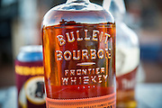 SHOT 10/16/16 6:21:37 PM - Bulleit bourbon at the ready while camping along the White Rim Trail. The White Rim is a mountain biking trip in Canyonlands National Park just outside of Moab, Utah. The White Rim Road is a 71.2-mile-long unpaved four-wheel drive road that traverses the top of the White Rim Sandstone formation below the Island in the Sky mesa of Canyonlands National Park in southern Utah in the United States. The road was constructed in the 1950s by the Atomic Energy Commission to provide access for individual prospectors intent on mining uranium deposits for use in nuclear weapons production during the Cold War. Four-wheel drive vehicles and mountain bikes are the most common modes of transport though horseback riding and hiking are also permitted.<br /> (Photo by Marc Piscotty / © 2016)