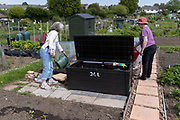 A mother and daughter water their veg at the family vegetable allotment plot, on 30th May 2021, in Nailsea, North Somerset, England.