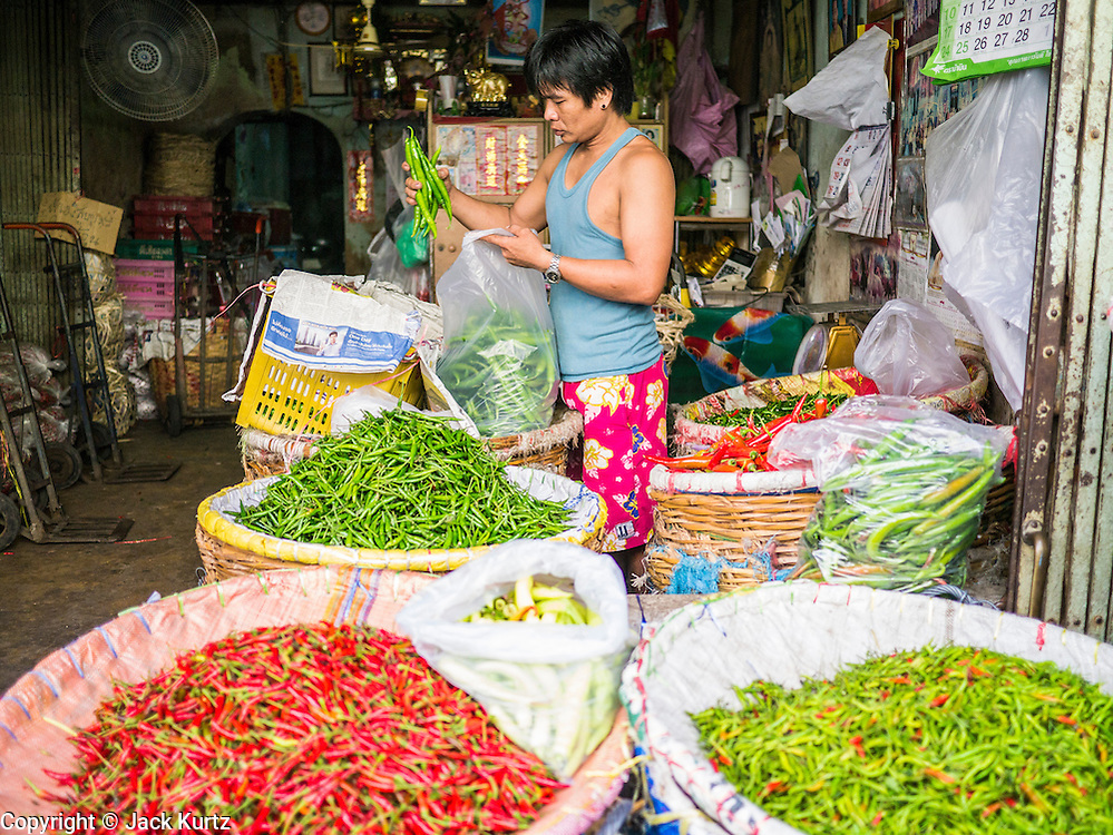 17 MAY 2013 - BANGKOK, THAILAND:   A chilies vendor bags his produce in the flower market in Bangkok. The Bangkok Flower Market (Pak Klong Talad) is the biggest wholesale and retail fresh flower market in Bangkok. It is also one of the largest fresh fruit and produce markets in the city. The market is located in the old part of the city, south of Wat Po (Temple of the Reclining Buddha) and the Grand Palace.   PHOTO BY JACK KURTZ