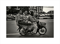Riding on the back of a motorbike in Phnom Penh, Cambodia's capital, I came across these two monks. I asked my driver to speed up so I could get a photograph, all the while wondering what party they were going to attend.<br /> Purchase a signed and numbered limited edition fine art print of this image from www.hanskemp.com/store