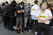 "In the 24hrs that a further 38 died from Coronavirus, bringing the total to 41,736, a further easing of the UK's Covid pandemic lockdown restrictions took place with many high street shops today being allowed to re-open after three months of forced closure. Prime Minister Boris Johnson, wanting to stimulate the economy, has urged people to ""shop with confidence"" and long queues formed outside the main brands. But unlike on public transport, face coverings are not compulsory so shop floors and shopping practices have had to be adapted to ensure customers' social distances, amid fears of a second infection wave. Young buyers queue outside Nikeworld and wait for opening time held in a pen  at Oxford Circus, on 15th June 2020, in London, England."