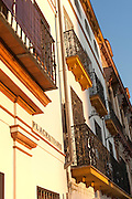 Late afternoon golden sunlight falling of historic houses in Placentines street, central Seville, Spain