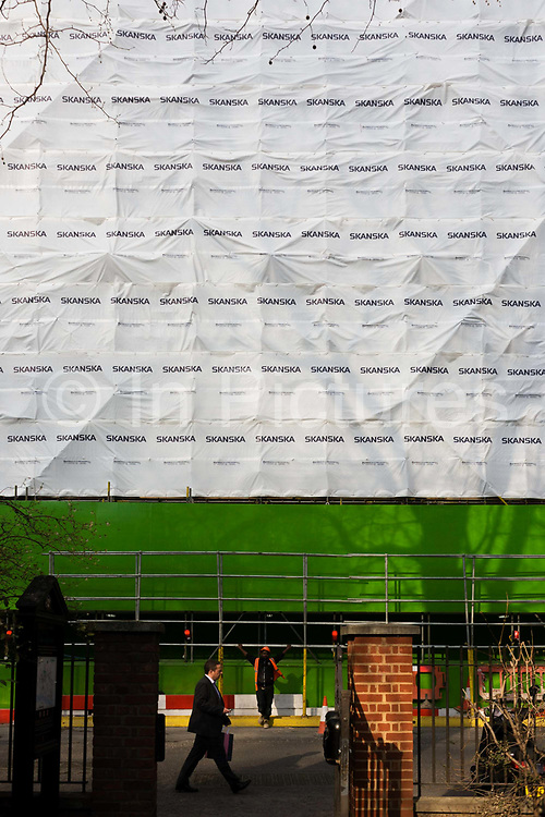 Construction safety sheeting with the shadow of a plain tree at a Skanska building project in Finsbury Circus. Whilst known mainly for large high-profile schemes, Skanska also undertake many smaller projects including public realm improvements, involved in some of the UK's most prestigious projects in both the Private and Public Sectors.