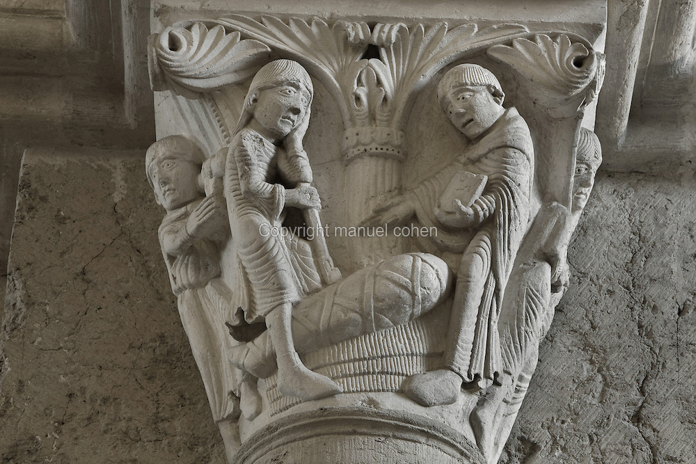 Carved capital from the narthex of Vezelay Abbey church, Vezelay, Yonne, Burgundy, France. Vezelay Abbey was a Benedictine and Cluniac monastery founded in the 9th century by St Badilo, who was said to have brought back relics of Mary Magdalene from the Holy Land. The Abbey Church or Basilica of St Mary Magdalene is a 12th century Burgundian Romanesque church. This capital depicts Saint Benedict resurrecting a boy. The Saint wears his tonsure and holds a book and blesses the body of the boy, wrapped in a shroud, while his grieving father watches. Picture by Manuel Cohen