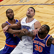 ORLANDO, FL - FEBRUARY 17:  Alec Burks #18 of the New York Knicks, Nikola Vucevic #9 of the Orlando Magic and Julius Randle #30 of the New York Knicks fight for a rebound at Amway Center on February 17, 2021 in Orlando, Florida. NOTE TO USER: User expressly acknowledges and agrees that, by downloading and or using this photograph, User is consenting to the terms and conditions of the Getty Images License Agreement. (Photo by Alex Menendez/Getty Images)*** Local Caption *** Alec Burks; Nikola Vucevic; Julius Randle