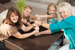 Happy family making a tower stack of their hands and fists in a team effort of cooperation, Bavaria, Germany